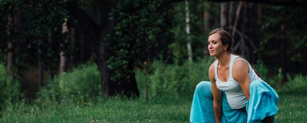 A pregnant woman with flowing aqua blue pants and white singet in a yogic squat on green grass with trees behind